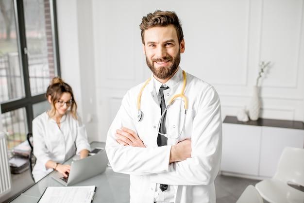 Porträt eines eleganten oberarztes im medizinischen kittel mit junger assistentin im hintergrund im weißen büroinnenraum