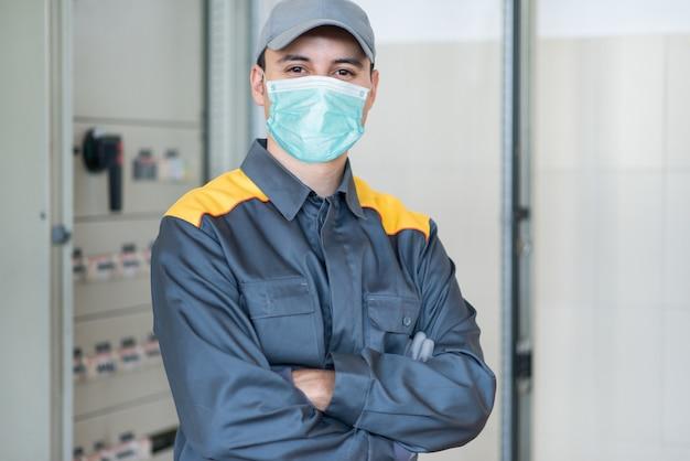 Porträt eines elektrikers vor einer industriellen schalttafel in einer fabrik beim tragen einer maske