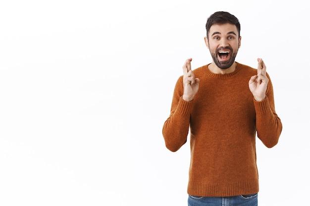 Porträt eines enthusiastischen, wunschvollen und glücklichen jungen kaukasischen mannes mit bart, der freude und gute nachrichten vorwegnimmt, investitionen in etwas tätigt, hoffnung bringen geld, daumen drücken und warten