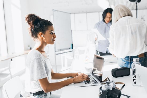 Porträt eines entspannten freiberuflichen arbeiters, der musik in kopfhörern hört und mit laptop arbeitet. porträt junger spezialisten internationaler unternehmen, die zeit in einem gemütlichen büro verbringen.