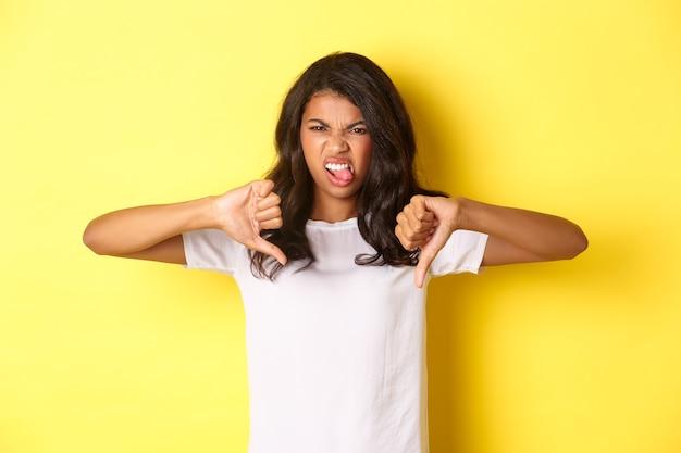 Porträt eines enttäuschten afroamerikanischen teenager-mädchens, das zunge von abneigung und daumen nach unten zeigt
