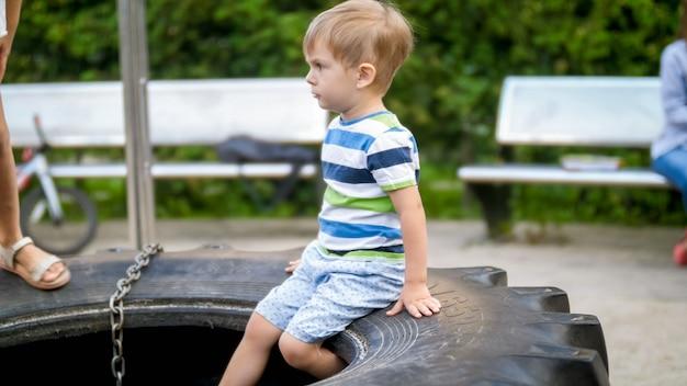 Porträt eines entzückenden 3-jährigen kleinen jungen, der auf dem großen gummirad auf dem spielplatz sitzt