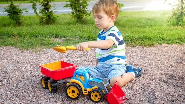 Porträt eines entzückenden 3-jährigen kleinkindjungen, der mit spielzeug-lkw mit anhänger auf dem spielplatz im park spielt. kind gräbt und baut aus sand
