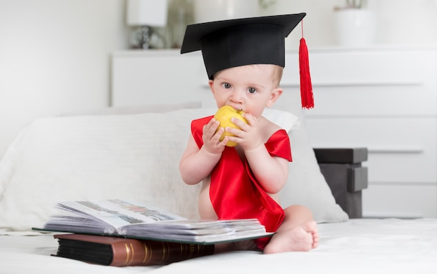 Porträt eines entzückenden babys in abschlusskappe, das aus büchern und beißendem apfel sitzt. konzept des babys, das klüger wird