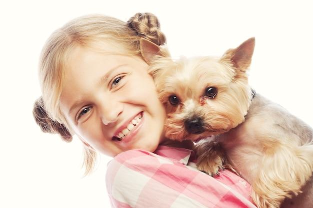 Porträt eines entzückenden jungen mädchens lächelnd, das yorkshire terrier welpen hält