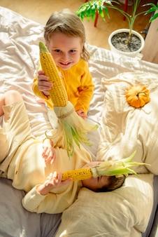 Porträt eines entzückenden kindes, das einen mais hält Premium Fotos