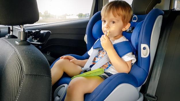 Porträt eines entzückenden kleinkindjungen, der im kindersitz sitzt und kekse isst