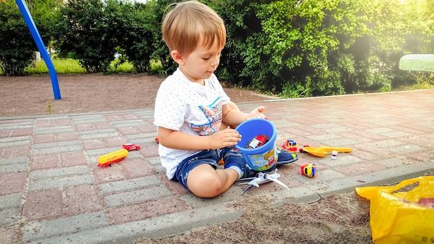 Porträt eines entzückenden kleinkindjungen, der mit vielen bunten spielsachen auf dem kinderspielplatz spielt