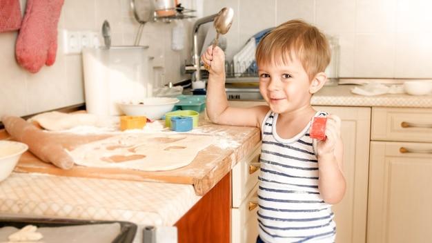 Porträt eines entzückenden lächelnden 3-jährigen jungen, der einen großen löffel in der küche hält, während er kocht und in die kamera schaut
