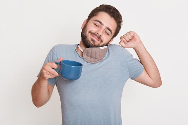 Porträt eines entzückten entspannten gutaussehenden jungen mannes, der die augen schließt, aufwacht, eine schlafmaske um den hals hat, einen arm hebt und eine faust hat