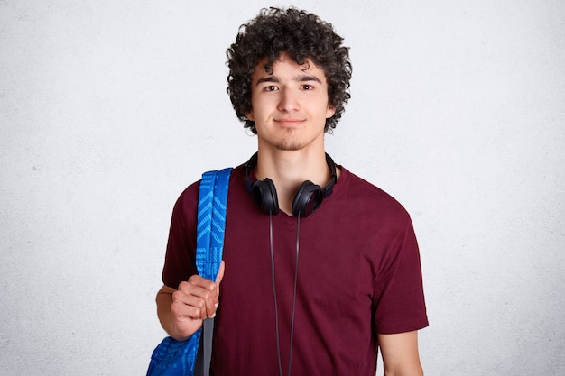Porträt eines entzückten männlichen hipster-studenten mit knackigem haar