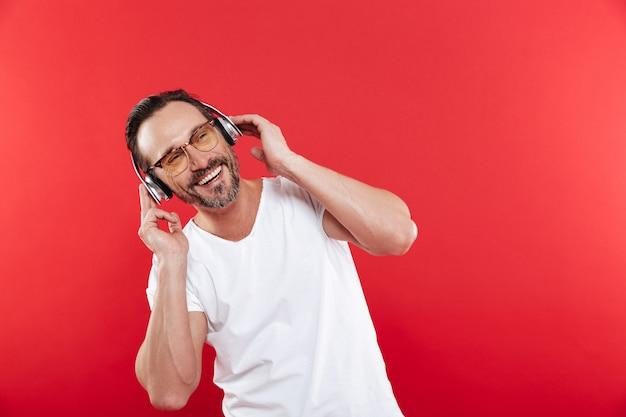 Porträt eines entzückten reifen mannes, der musik hört