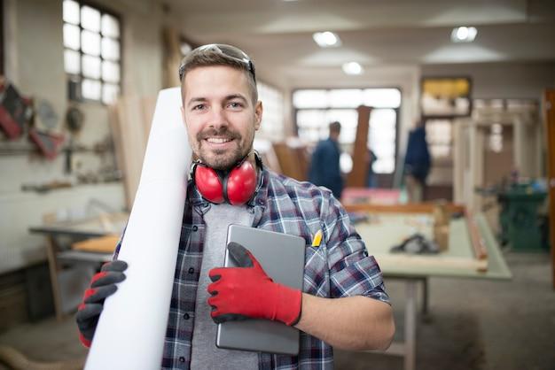 Porträt eines erfahrenen architekten, der tabletten- und projektentwurfspapiere in der werkstatt hält