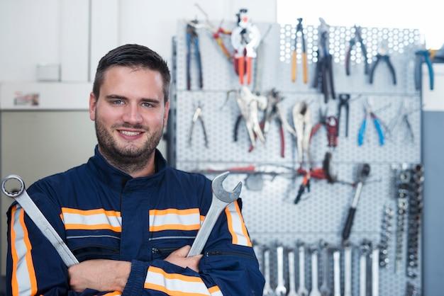 Porträt eines erfahrenen lächelnden automechanikers, der schraubenschlüssel in der werkstatt hält