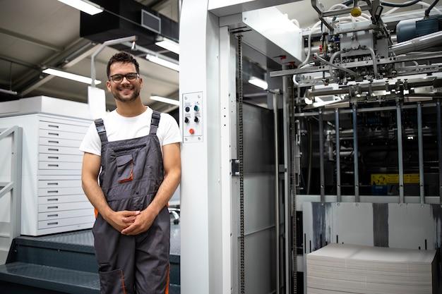 Porträt eines erfahrenen typographen, der in der druckerei an einer modernen druckmaschine steht.