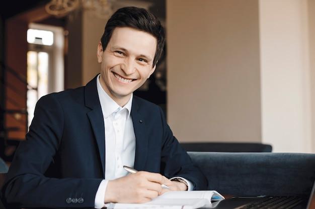 Porträt eines erfolgreichen geschäftsmannes, der an seinem schreibtisch sitzt und etwas in notizbuch schreibt, während er die kamera lächelnd betrachtet.