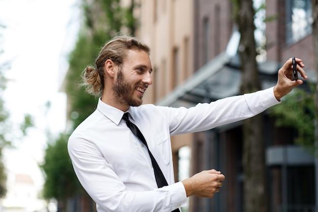 Porträt eines erfolgreichen geschäftsmannes, der ein selfie nimmt und lächelt. ein lockiger manager in weißem hemd und krawatte macht glücklich ein selfie mit einer handykamera.