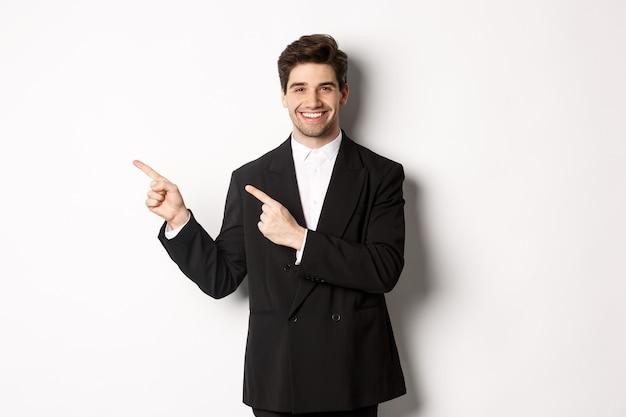 Porträt eines erfolgreichen, gutaussehenden geschäftsmannes im anzug, der mit den fingern auf die obere linke ecke zeigt und lächelt, werbung zeigt, auf weißem hintergrund steht