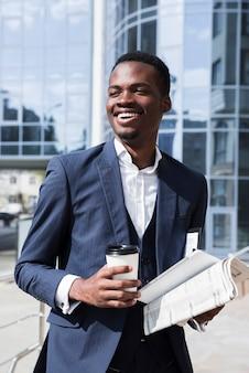 Porträt eines erfolgreichen jungen afrikanischen geschäftsmannes, der wegwerfkaffeetasse hält; zeitung und digitales tablet