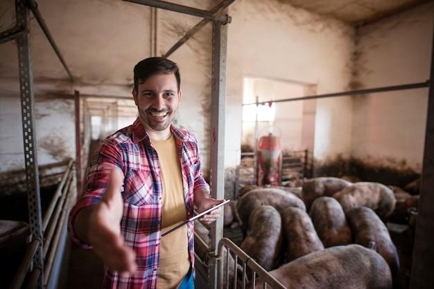 Porträt eines erfolgreichen schweinezüchters, der eine zitternde hand gibt