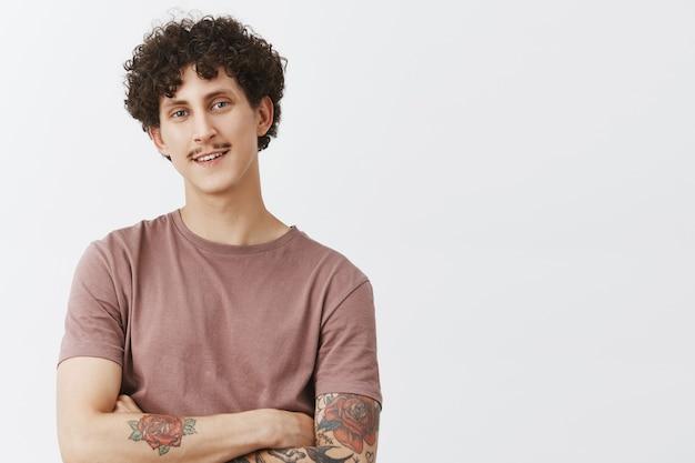 Porträt eines erfreuten und entzückten gutaussehenden jungen mannes mit schnurrbart-tätowierungen und lockiger frisur, die von glücklichen und zufriedenen gefühlen lächelt