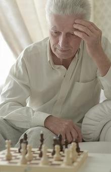 Porträt eines ernsten älteren mannes, der schach spielt