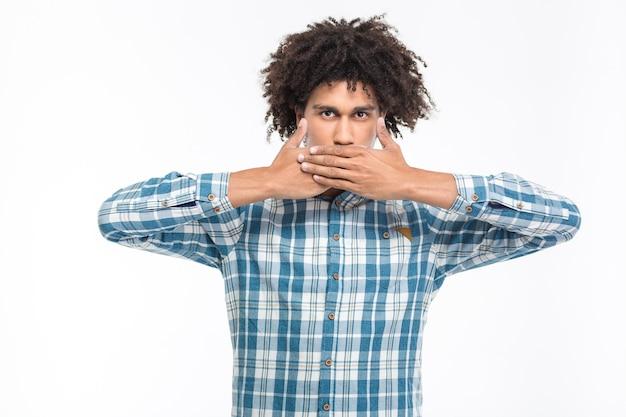 Porträt eines ernsten afroamerikanischen mannes, der seinen mund mit handflächen bedeckt, isoliert auf einer weißen wand