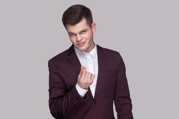 Porträt eines ernsten, gutaussehenden jungen mannes in violettem anzug und weißem hemd, stehend, in die kamera schauend und geldgeste zeigend. indoor-studioaufnahme, auf grauem hintergrund isoliert.