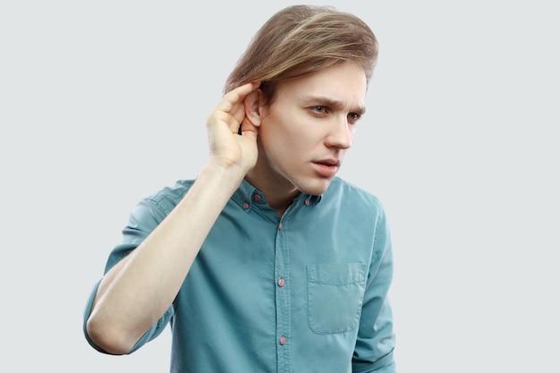 Porträt eines ernsten, gutaussehenden, langhaarigen, blonden jungen mannes in blauem freizeithemd, der die hand am ohr hält und versucht, zu hören oder auszuspionieren. indoor-studioaufnahme, isoliert auf hellgrauem hintergrund.