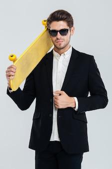 Porträt eines ernsten jungen geschäftsmannes mit sonnenbrille, der gelbes skateboard auf seiner schulter über grauer wand hält