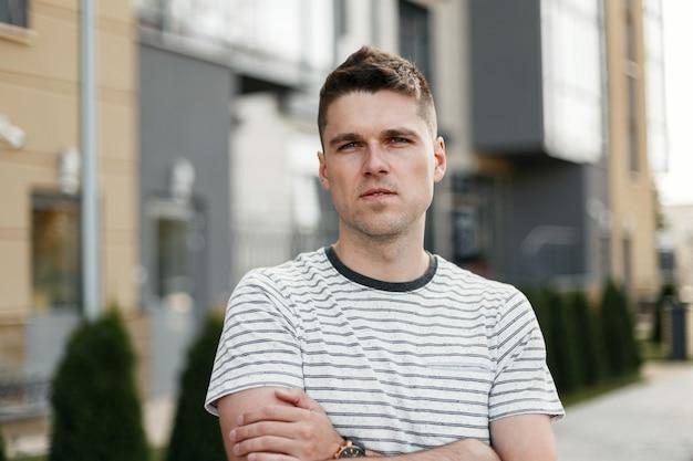 Porträt eines ernsten jungen mannes mit einer modischen frisur in einem stilvollen gestreiften t-shirt auf dem hintergrund eines modernen gebäudes