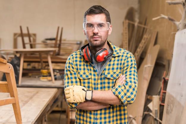 Porträt eines ernsten männlichen tischlers, der in der werkstatt steht