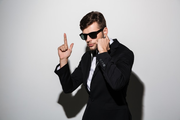 Porträt eines ernsten mannes in kopfhörern und sonnenbrille