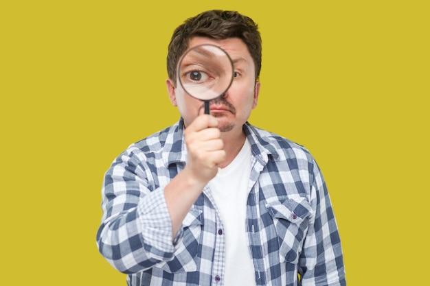 Porträt eines ernsten mannes mittleren alters in lässig kariertem hemd, der eine lupe hält und die kamera mit großem zoom-auge betrachtet. innenstudio erschossen, auf gelbem hintergrund isoliert.