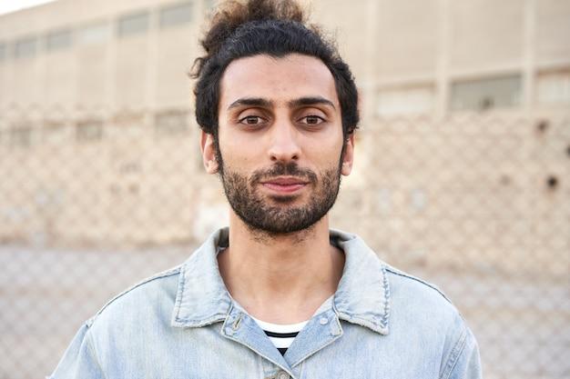 Porträt eines ernsten moslemischen jungen mannes, der kamera betrachtet