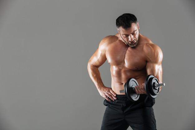 Porträt eines ernsten starken hemdlosen männlichen bodybuilderhebens