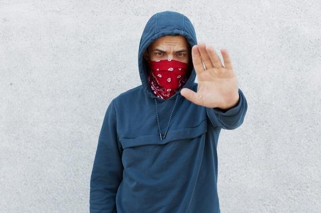 Porträt eines ernsthaft enttäuschten demonstranten gegen die gesetzlosigkeit der schwarzen bürger, ein typ, der mit seiner handfläche eine stoppgeste zeigt, die mordmorde stoppt, ein aktivist, der einen pullover mit kapuzenpulli und bandana-maske trägt.