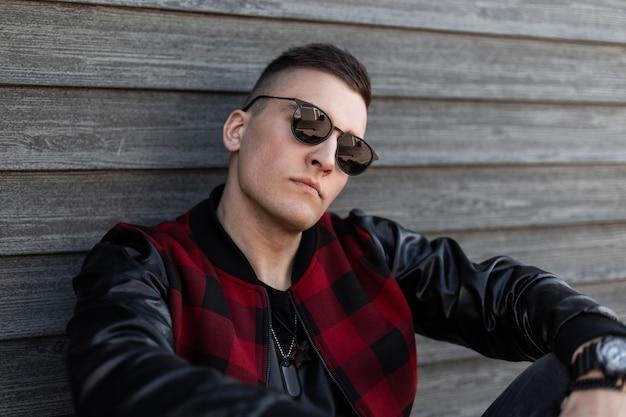 Porträt eines ernsthaften attraktiven jungen hipster-mannes in stilvoller dunkler sonnenbrille mit einer trendigen frisur in einer stilvollen rot karierten jacke mit lederärmeln an der vintage-wand