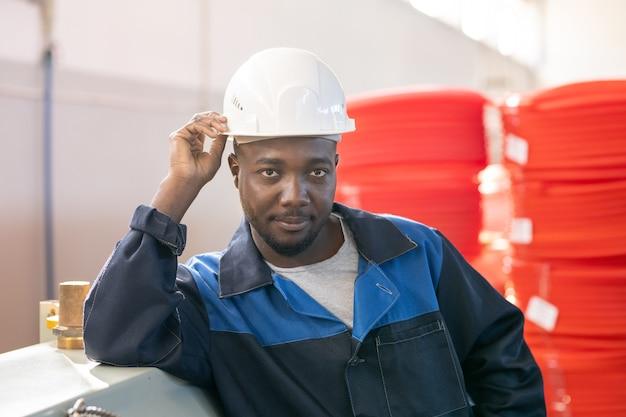 Porträt eines ernsthaften bärtigen fertigungsarbeiters in bauarbeiterhelm und overall, der bei der vorbereitung auf die metallarbeiten sicherheitsarbeitshandschuhe anzieht