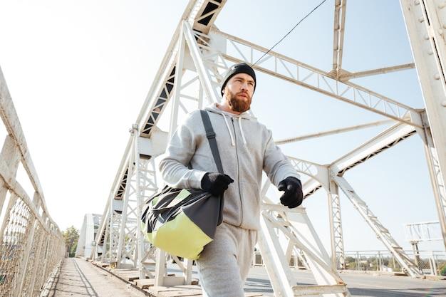 Porträt eines ernsthaften bärtigen sportlers mit sporttasche, der entlang der städtischen brücke geht