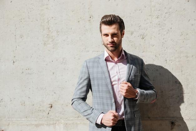 Porträt eines ernsthaften gutaussehenden mannes in einer jacke stehend