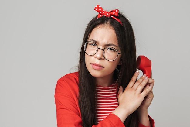 Porträt eines ernsthaften jungen mädchens, isoliert über grauer wand, das mit roter retro-telefonabdeckung mit der hand spricht, um zu versuchen, sie zu hören?