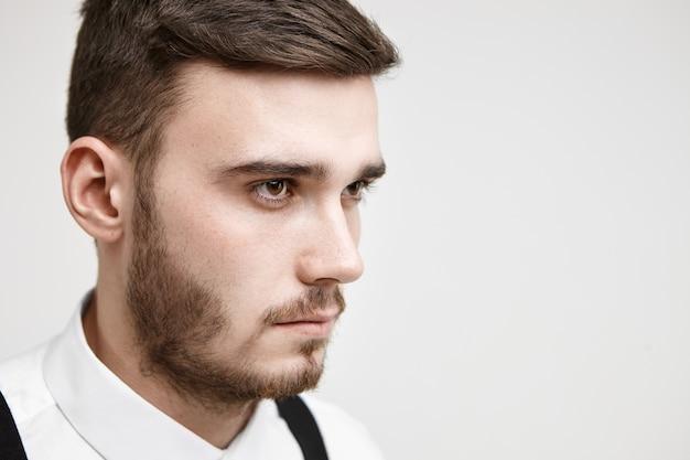Porträt eines ernsthaften, konzentrierten jungen managers mit borsten, der mit konzentriertem, entschlossenem gesichtsausdruck vor ihm schaut und bereit für harte arbeit ist. job-, karriere-, wettbewerbs- und herausforderungskonzept