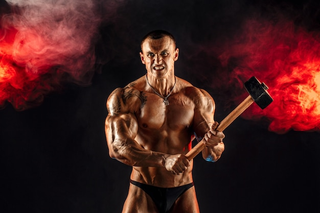 Porträt eines ernsthaften muskulösen topless mannes mit vorschlaghammer