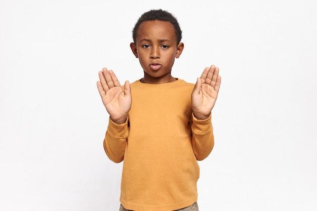 Porträt eines ernsthaften, selbstbewussten afroamerikanischen schülers im sweatshirt, der seine hände mit offenen handflächen ausstreckt und eine stoppgeste macht