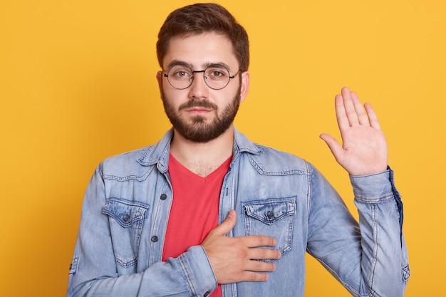 Porträt eines ernsthaften zuversichtlichen magnetischen jungen mannes, der direkt eine hand hebend betrachtet, eine hand zu herzen legt und eid leistet