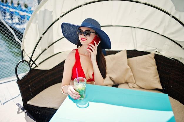 Porträt eines erstaunlichen mädchens im roten bikinibadeanzug und in der sonnenbrille sprechend an ihrem telefon beim sitzen auf dem sofa auf dem kai durch den see.