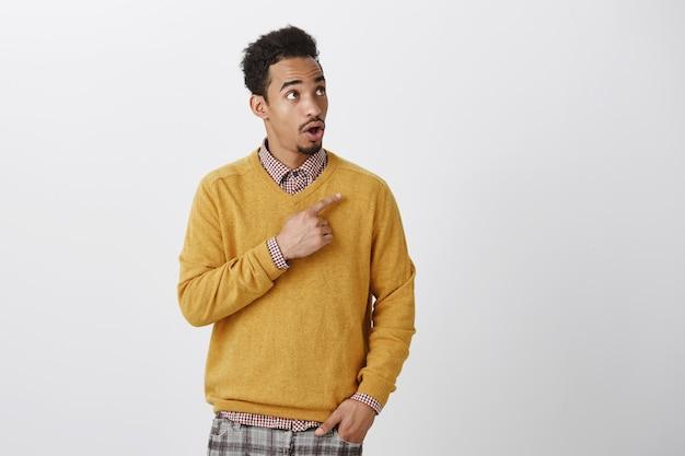 Porträt eines erstaunten gutaussehenden afroamerikaners mit afro-frisur, die auf die obere rechte ecke zeigt, kiefer fallen lässt und wow sagt