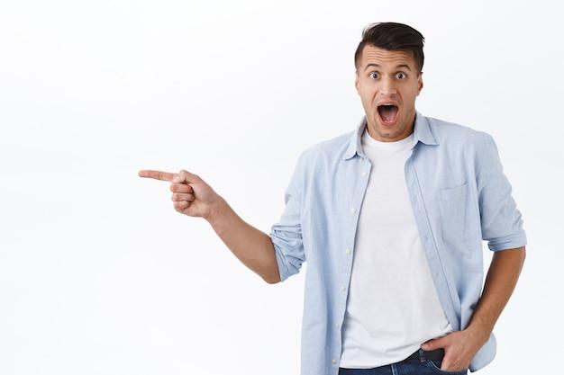 Porträt eines erstaunten, gutaussehenden kaukasischen mannes reagiert beeindruckt und wundert sich über ein neues tolles produkt auf lager, zeigt mit dem finger leer platz für ihre promo, schreit vor aufregung Premium Fotos