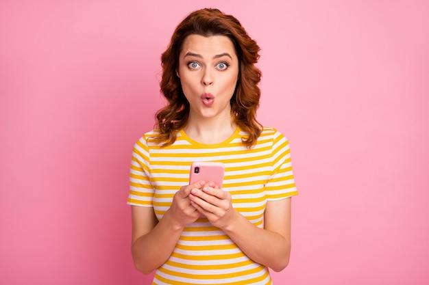 Porträt eines erstaunten mädchens, das eine schnelle verbindung verwendet, einzeln auf rosafarbenem hintergrund